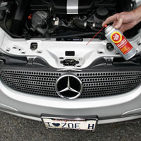 Man applying Fluid Film on Automobile Locks, Hinges, and Tracks